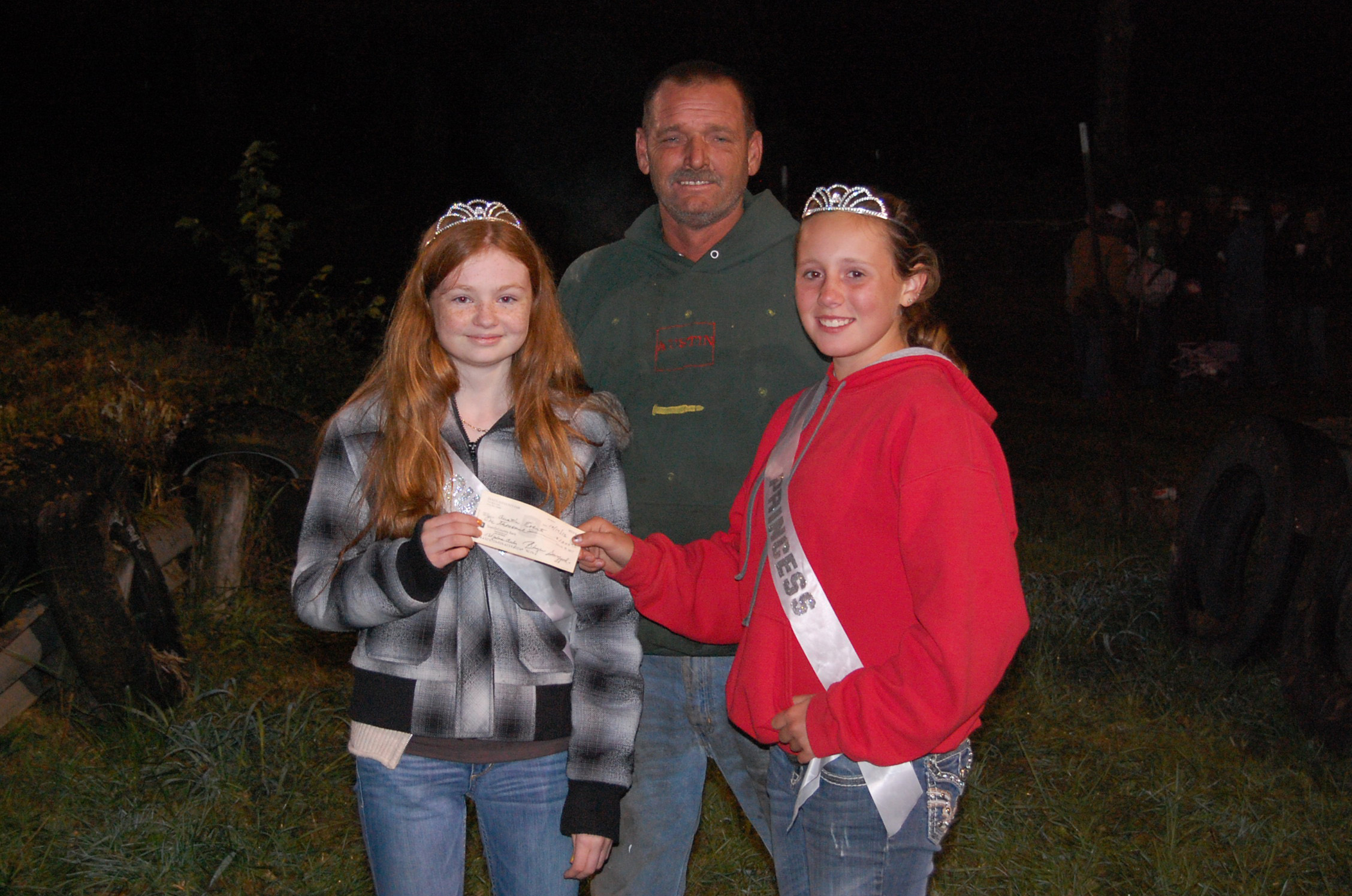 Demolition derby winner Austin Roberts, of Forsyth, is pictured here with Denim Gals Queen Crystal Fuller and Princess Dallee Sheppard, who will hand Roberts the $1,000 winner-take-all check.
