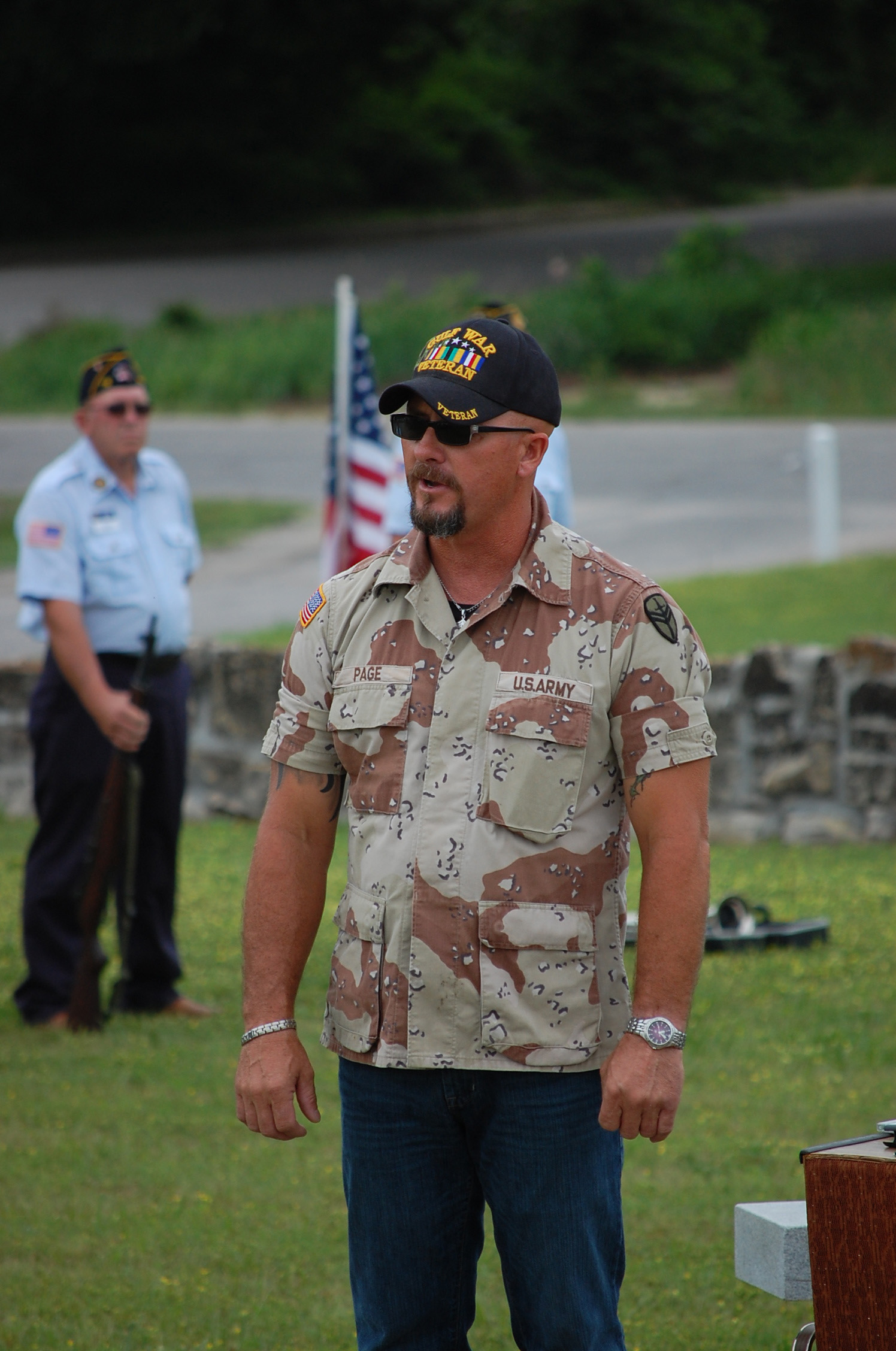 """Army veteran Bobby Page sings """"God Bless the USA"""" at the Ava Cemetery Monday morning."""